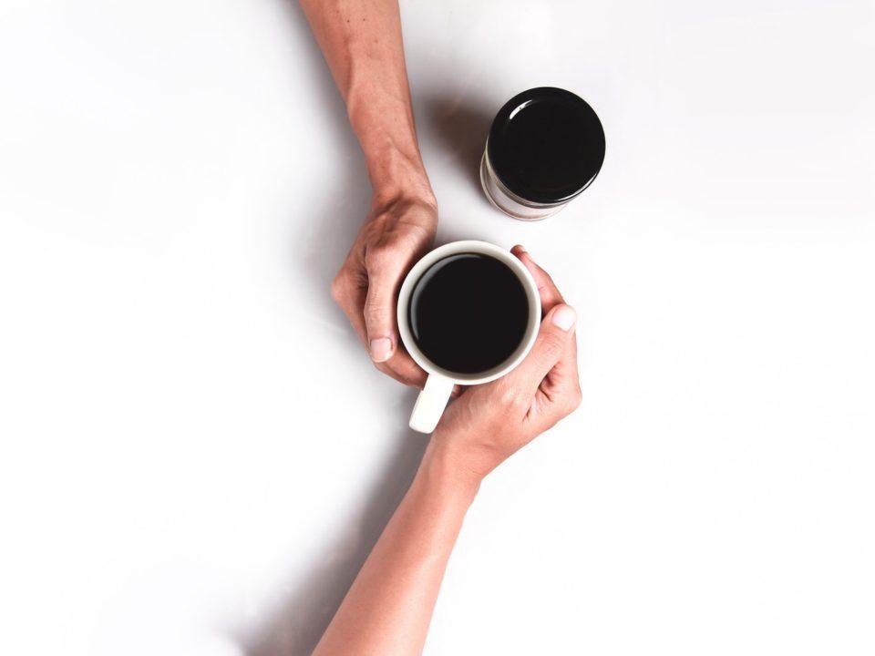 kaksi kahvikuppia ja kättä