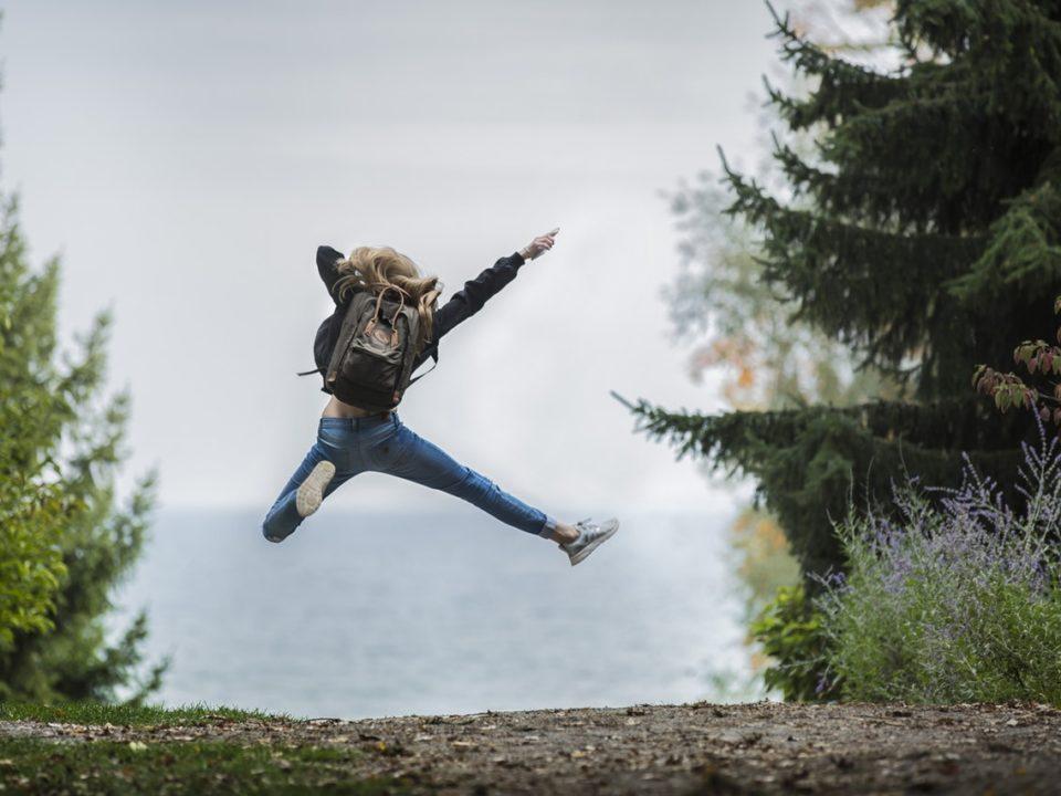 nainen ruskea reppu siniset farkut metsätie vesi ilmahyppy