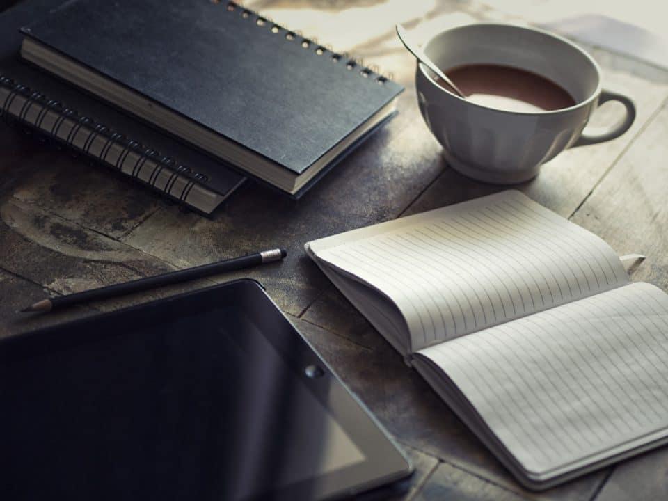 puinen pöytä kahvikuppi vihko tabletti kynä