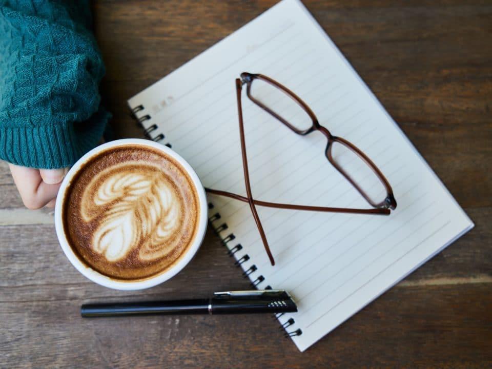 kahvikuppi käsi ruskeat silmälasit