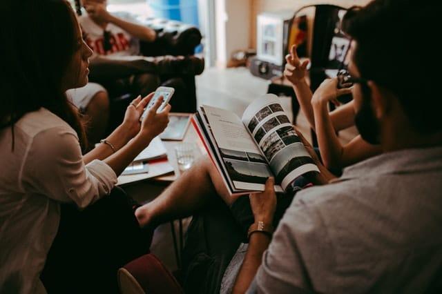 ihmisiä lehtiä ja kännykkää lukemassa