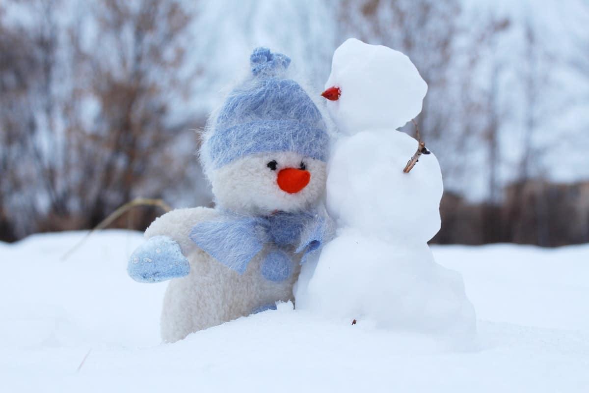 sinimyssyinen lumiukko halaa toista lumiukkoa