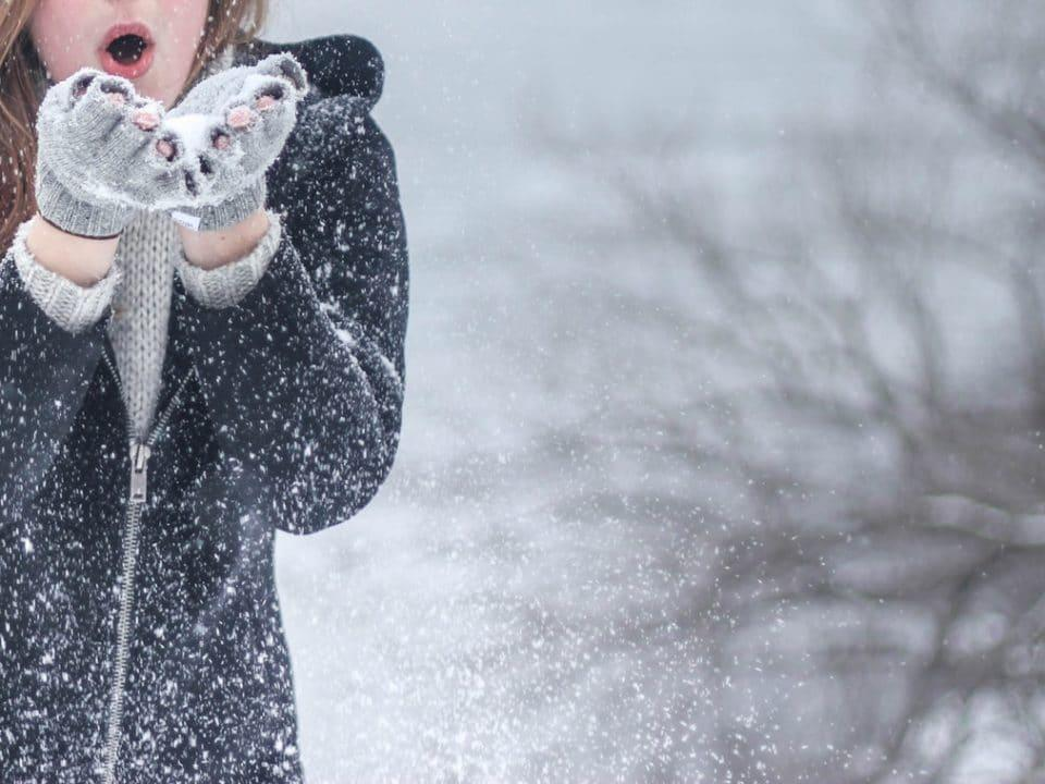 nainen puhaltaa käsistään lunta lumisessa maisemassa