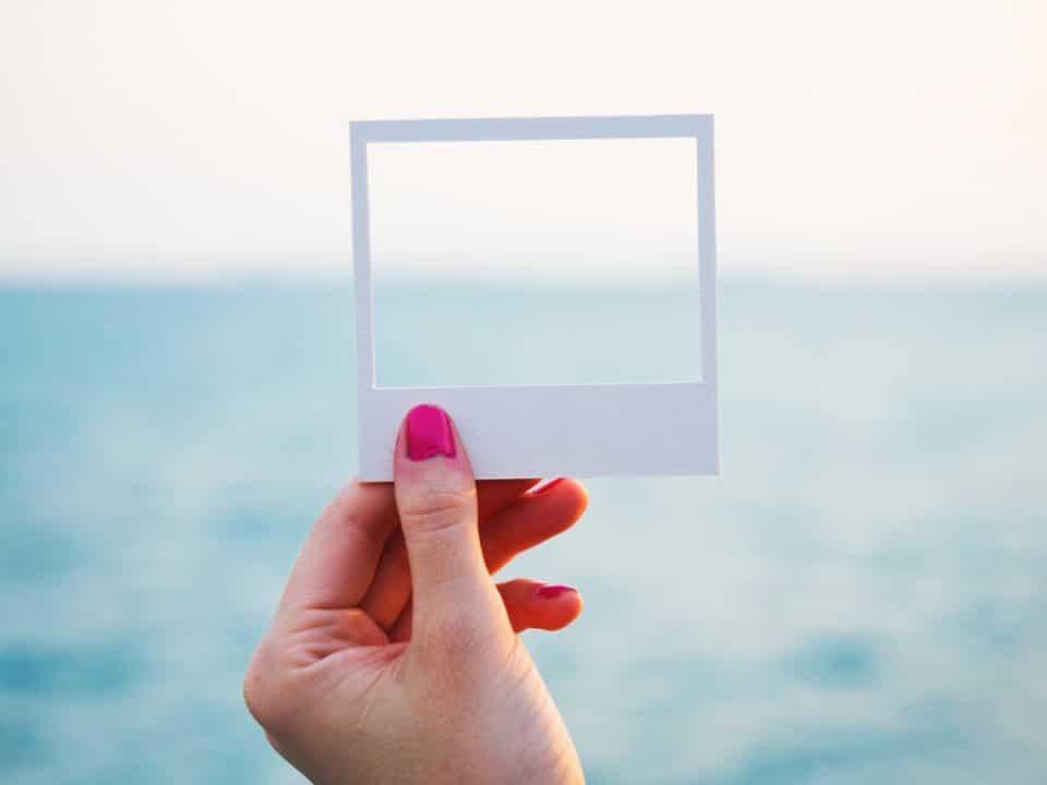 naisen käsi pitää kehystä merta ja taivasta vasten