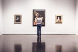 nainen katsoo selin kolmea maalausta
