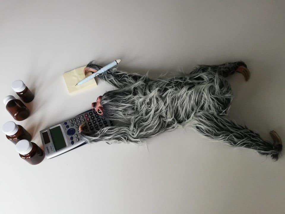 pehmolaiskiainen tekee laskelmia lattialla pilleripurkkien ympäröimänä