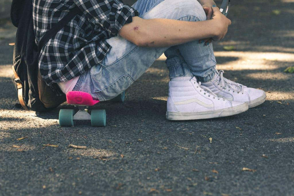 reppuselkäinen nuori istuu maassa skeittilaudan päällä