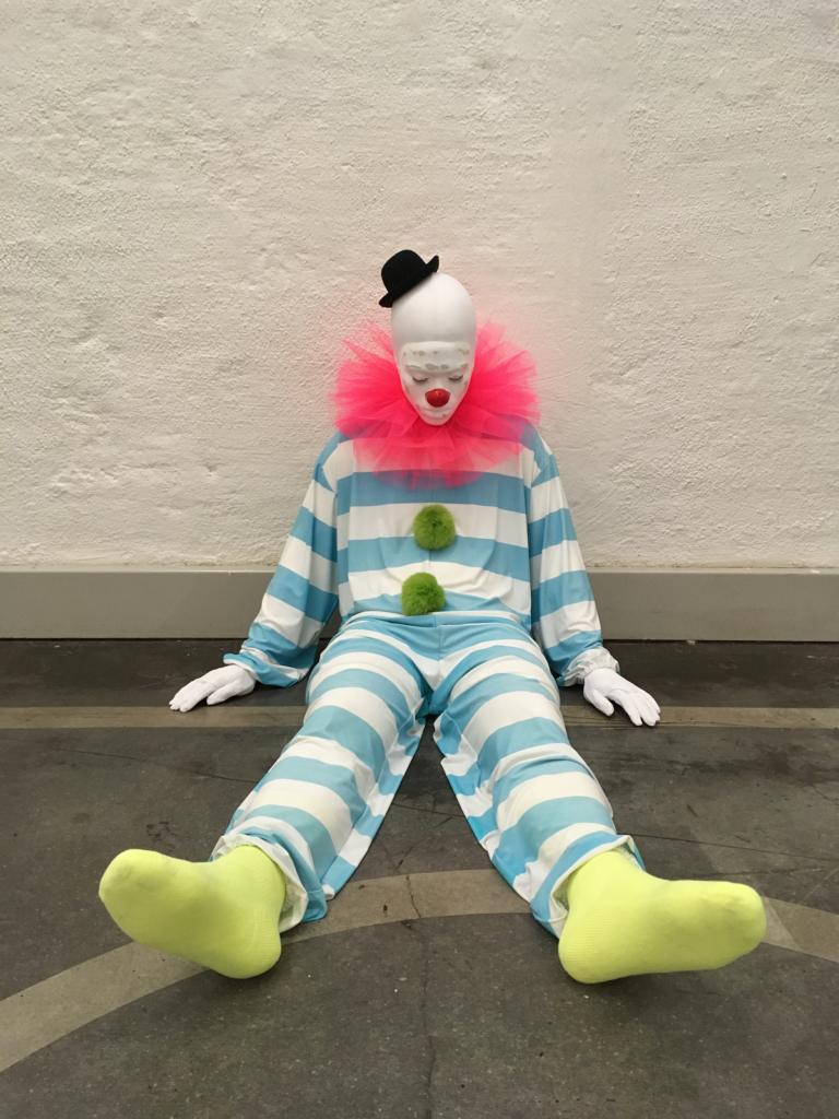 ugo rondinone klovni sinivalkoraitaisessa asussa istuu jalat suorina seinää vasten