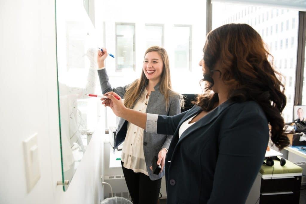 kaksi naista kirjoittaa taululle hymysuin toimistossa