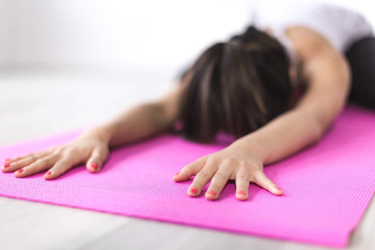 nainen tekee pilatesharjoituksia vaaleanpunaisella matolla