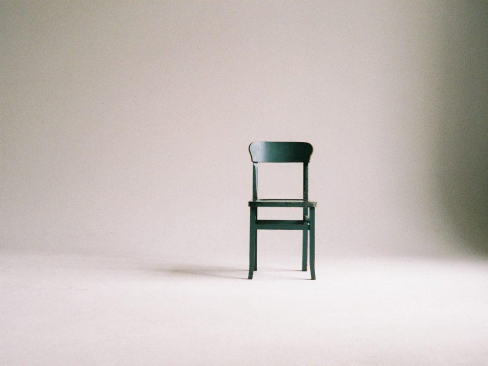 vihreä tuoli tyhjässä värittömässä huoneessa