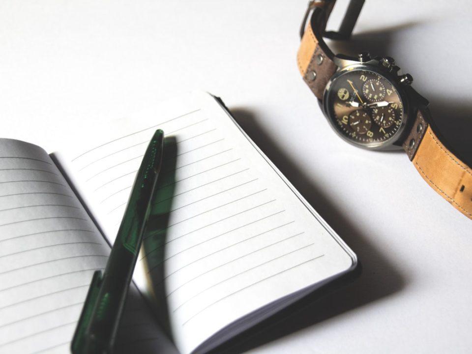valkoinen muistivihko kynä ja rannekello