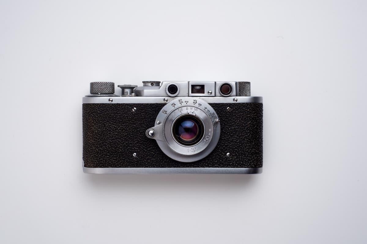 mustanharmaa vanhanaikainen kamera valkoista taustaa vasten