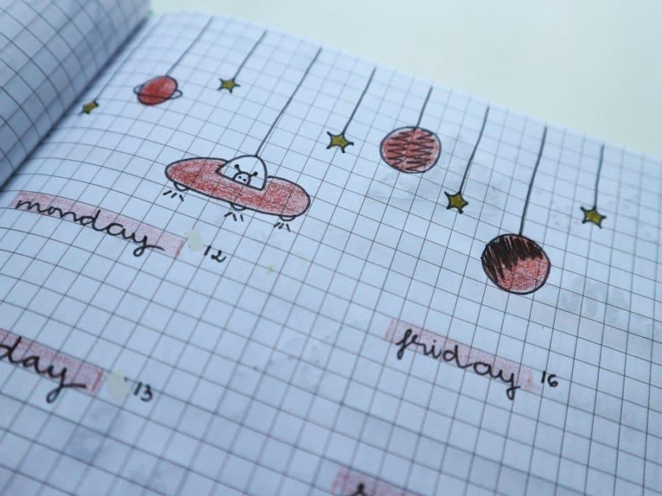 ruutuvihkoon tehty omatekoinen kalenteri avaruusteemaisine piirroksineen