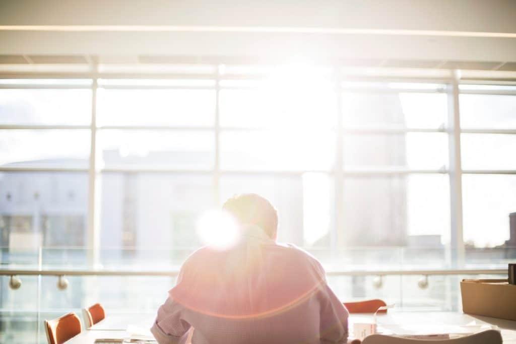 kauluspaitainen mies istuu työpöydän ääressä vastavalossa