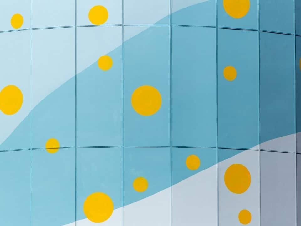 kaartuva pinta, jossa keltaisia ympyröitä ja sinisiä ja vaaleita läiskiä