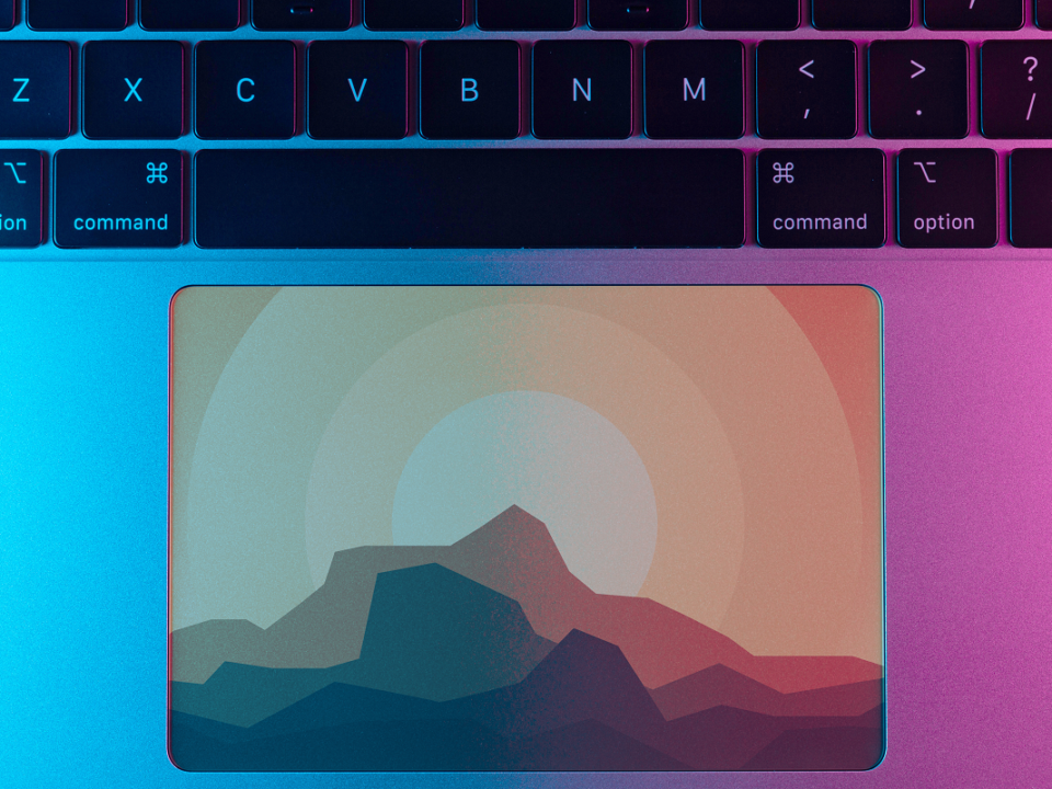 sinivioletti lähikuva näppäimistöstä, jossa hiiren liikuttimessa kuva auringonlaskusta vuorten taakse