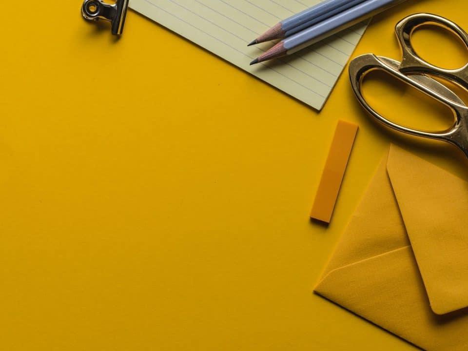 retroväritetty kuva keltaisella pinnalla kyniä, kirjekuori, muistilehtiö ja sakset