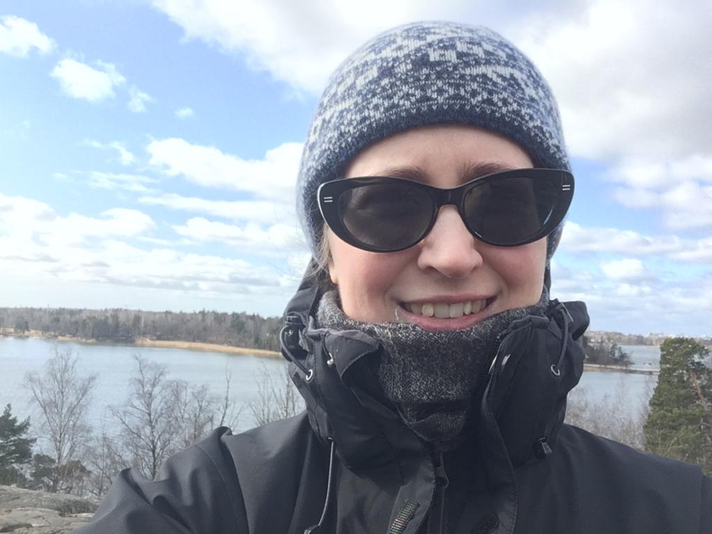 Emma Anderssonin kasvokuva huhtikuulta 2020 kalliomaisemissa takana Seurasaari ja Seurasaarenlahti