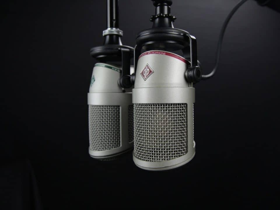 aluminista tehdyt katosta roikkuvat mikrofonit mustaa taustaa vasten