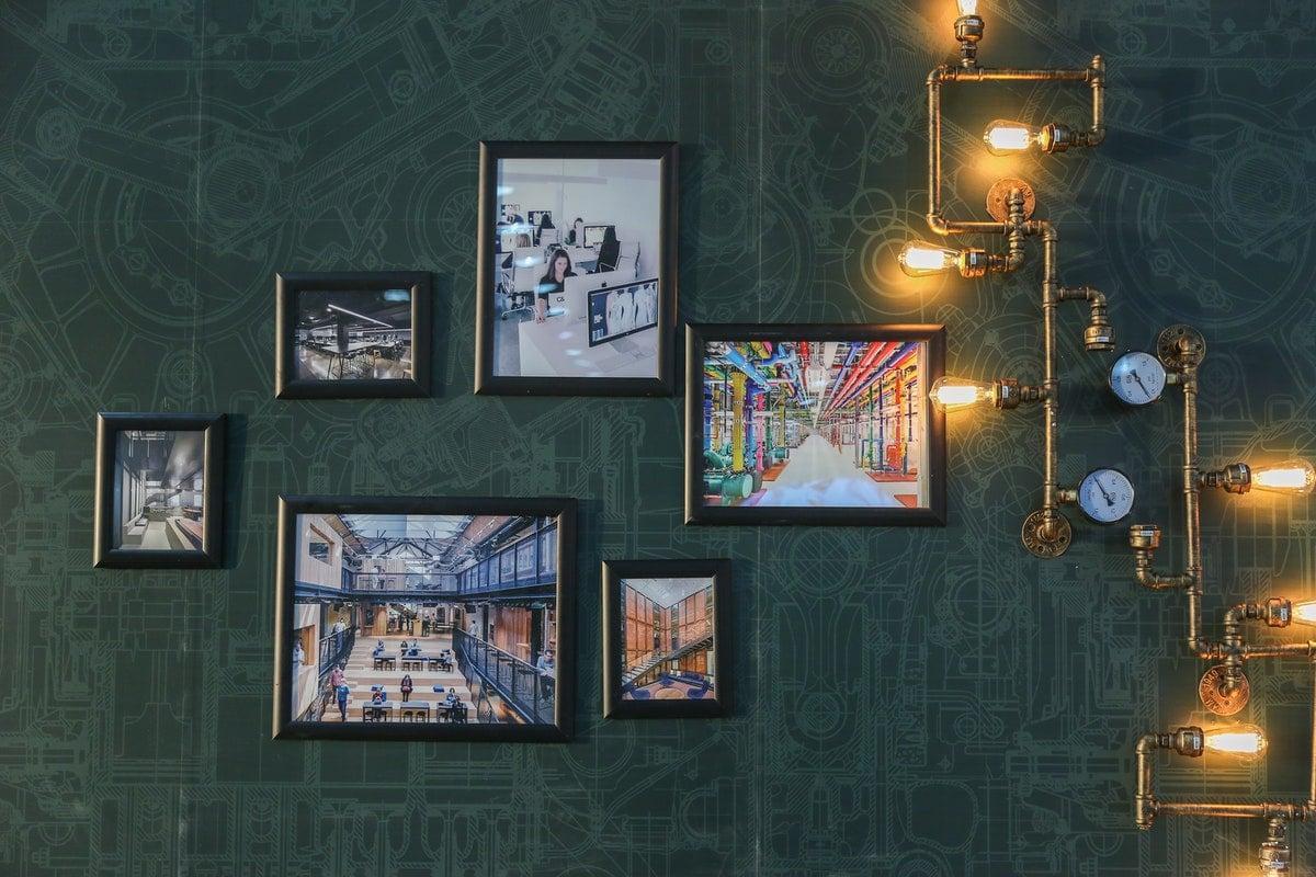 vihreällä seinällä kehystettyjä taideteoksia ja riippuvia valaisimia