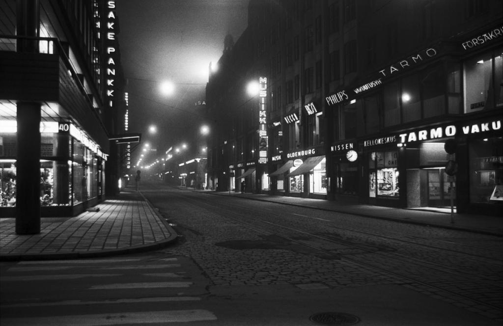 Aleksanterinkatu, näkymä illalla autiolta ja sumuiselta Aleksanterinkadulta Kluuvikadun kulmasta länteen. vuodelta 1970 Helsingin kaupunginmuseon kuvakokoelma