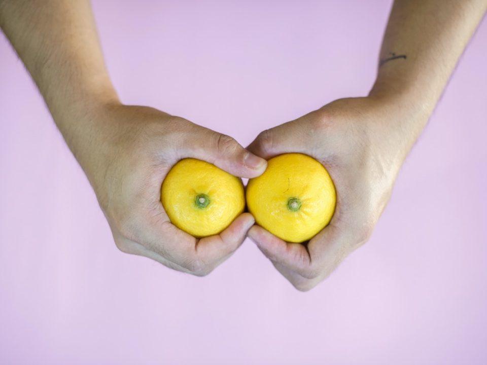 ihminen pitää käsissään kahta sitruunaa vaaleanpunaista taustaa vasten