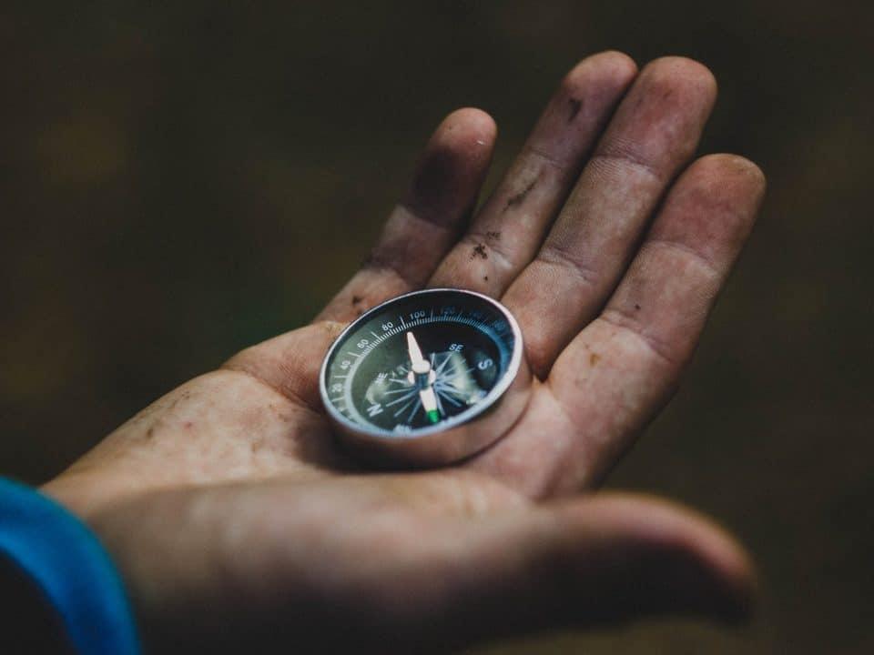 musta tausta ja kämmenellä pyöreä kompassi