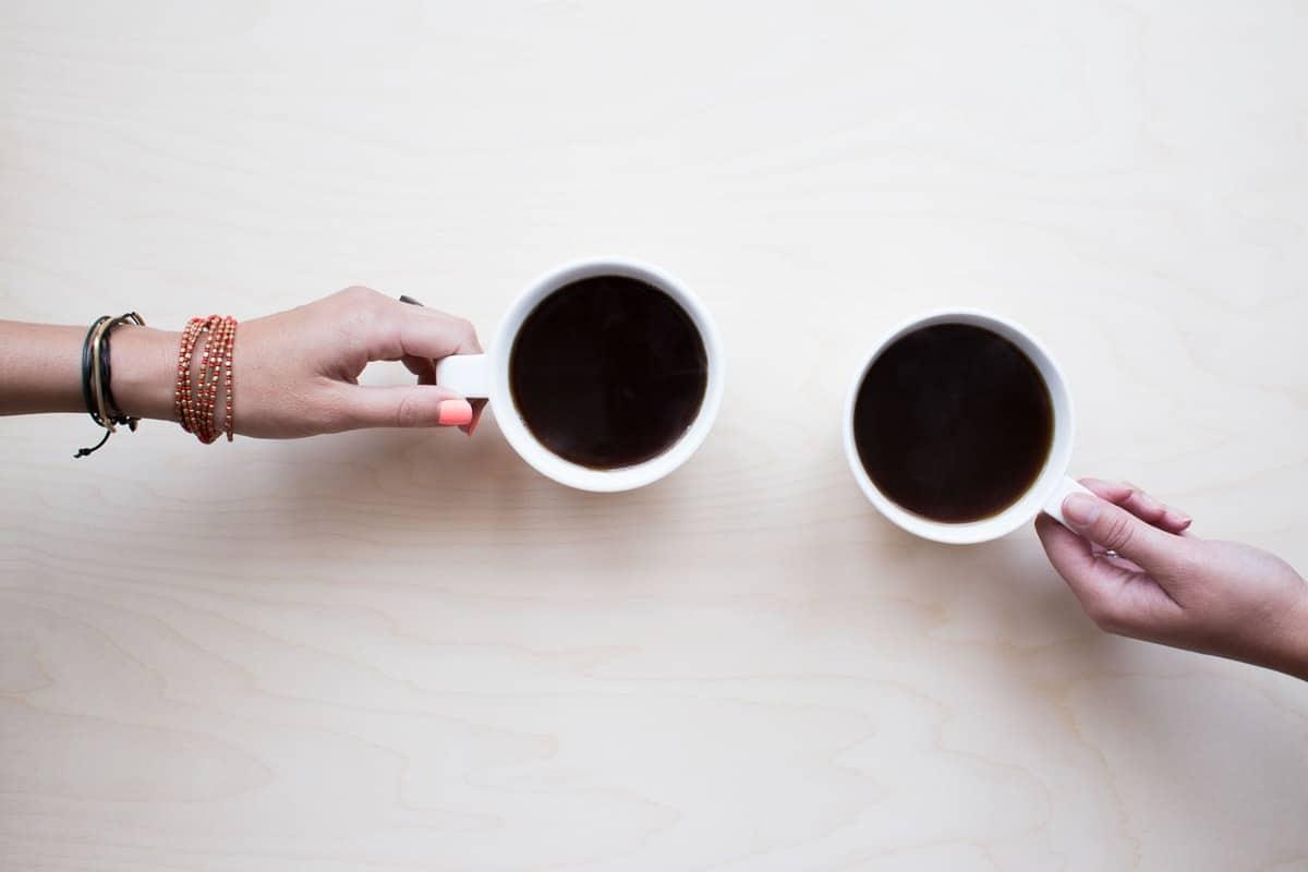 kuvakulma ylhäältä kahdesta kädestä, joilla on kahvikupit kädessä