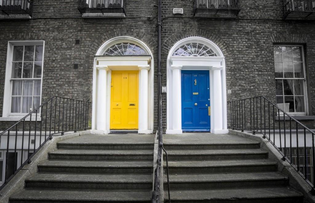 Irlannissa keltaiseksi ja siniseksi maalatut ovet muuten mustavalkoisessa kuvassa