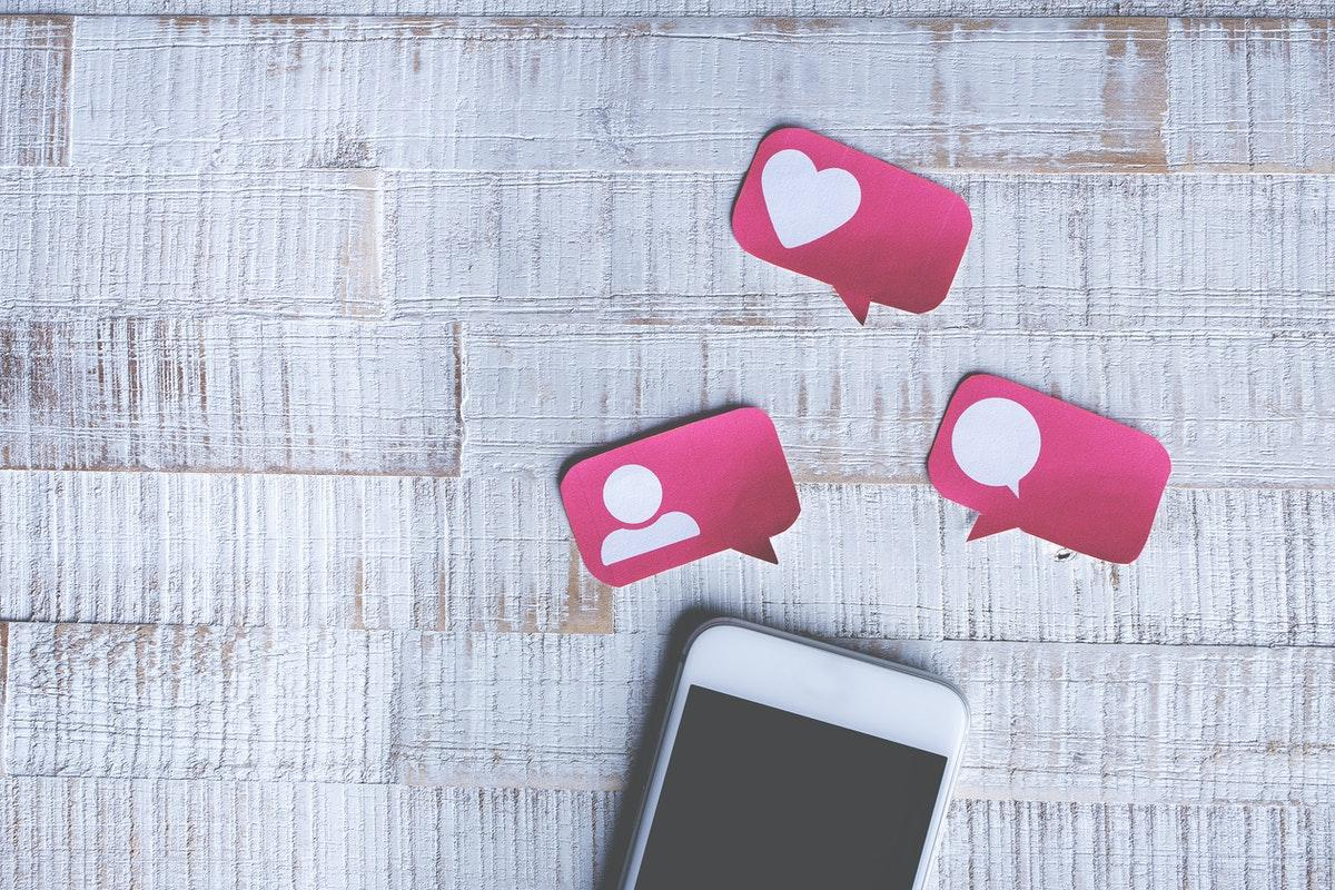kännykkä ja vaaleanpunaisia tykkäys- ja puhekuplalappusia harmaalla pöydällä