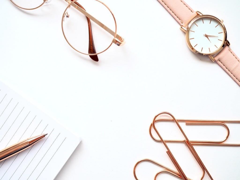 silmälasit, kello, klemmareita, kynä ja vihko valkoisella pinnalla